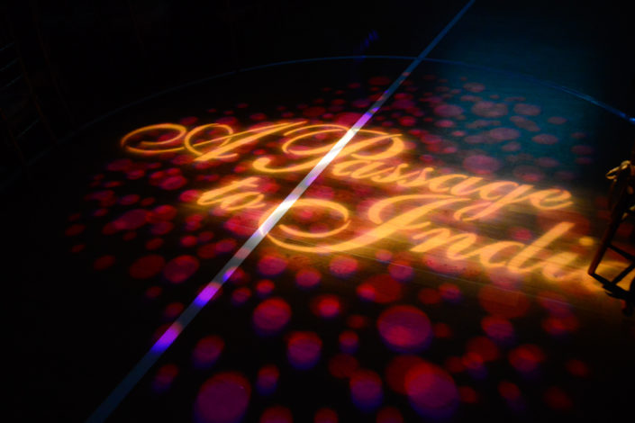 Text logo for A Passage to India Midwinter Ball is projected on the dance floor.