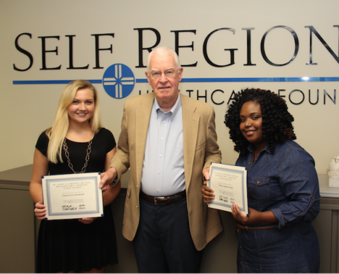 Scholarship recipients Kayla Cleveland (left)and Ebony Clark (right) receive their Scholarship certificates from John Heydel, Founder of the M. John and Drenda Heydel Respiratory Therapy Scholarship.