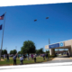Two military F-16 jets from South Carolina Air National Guard fly over the hospital building at Self Regional Healthcare. Operation American Resolve is a salute to healthcare workers, first responders and other essential workers during COVID-19 pandemic. On left, a flagpole flies the American flag and South Carolina state flag. On right is a portico for the hospital front entrance. In center, hospital employees and first responders stand on the lawn, look up, clap and wave at the jets.